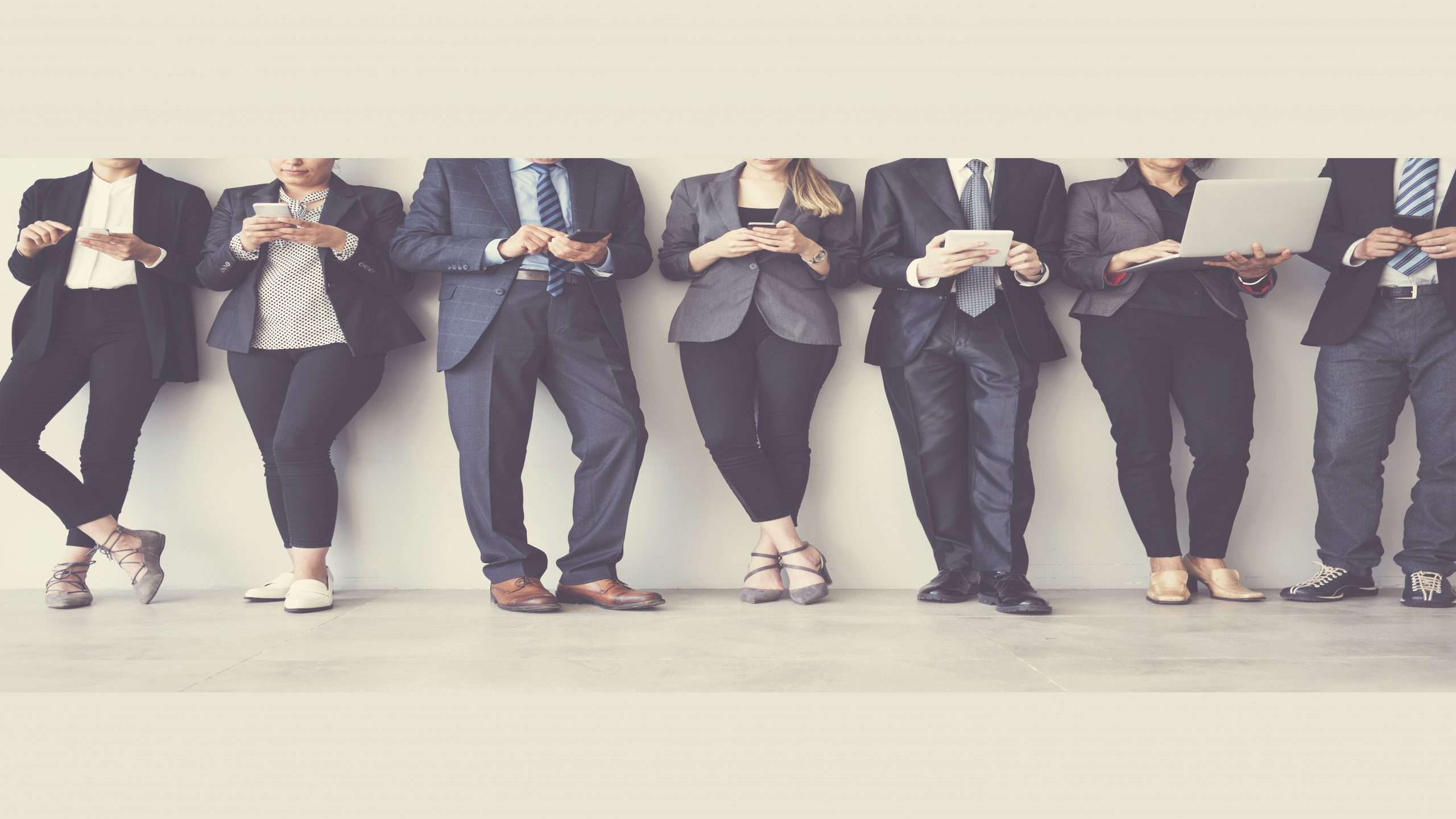 team of people in suits in a line with devices such as tablets and smartphones in their hands
